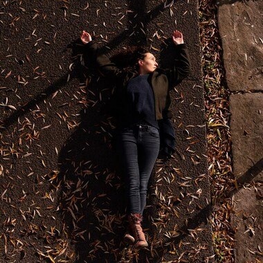Raquel Meseguer lies on the street. There are leaves all around her.