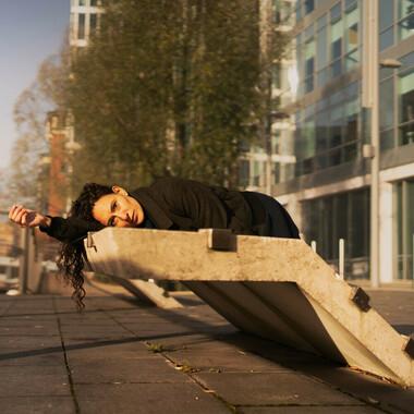 Raquel Meseguer liegt auf einem Betongebilde in der Stadt.
