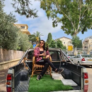 Samaa Wakeem sitzt auf einem Holzstuhl auf der Ladefläche eines Jeeps. Die Ladefläche ist mit Rasen ausgelegt. Im Hintergrund sind viele grüne Bäume und Pflanzen.