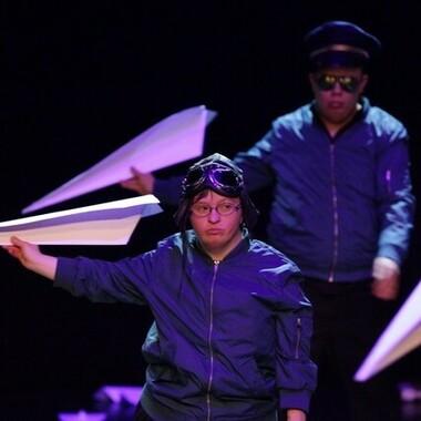 Zwei Performer*innen in Pilot*innen-Kostümen mit jeweils einem großen Papierflieger in der Hand.