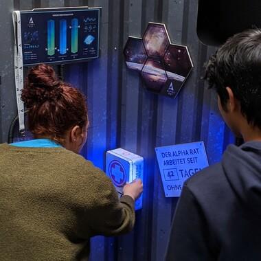 """Zwei Menschen erkunden einen Erste-Hilfe-Kasten. An der Wand hängt ein Schild: """"DER ALPHA RAT ARBEITET SEIT 43 TAGEN"""""""