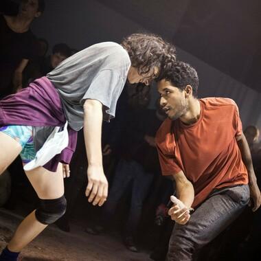Momentaufnahme von zwei tanzenden Menschen, die ihre Köpf aneinander gelegt haben und sich gegenseitig ins Gesicht schauen.