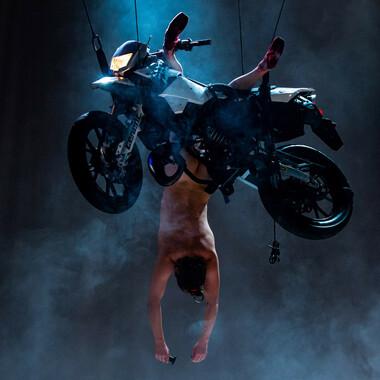 Ein Motorrad schwebt in der Luft. Eine Performerin hängt kopfüber von dem Motorrad herunter.
