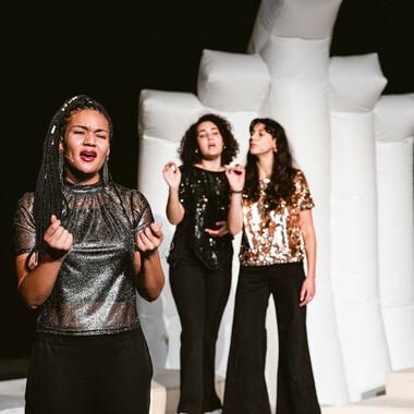 Eine Performerin singt und wird im Hintergrund von zwei weiteren Performerinnen begleitet.