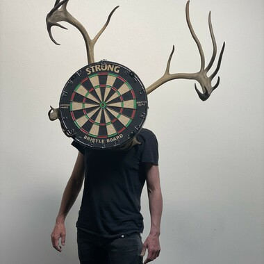 A body from the waist up. In front of the face is a dartboard with antlers.