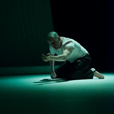 Michael Turinsky kniet in einem grünen Spotlight. Der Hintergrund ist dunkel.