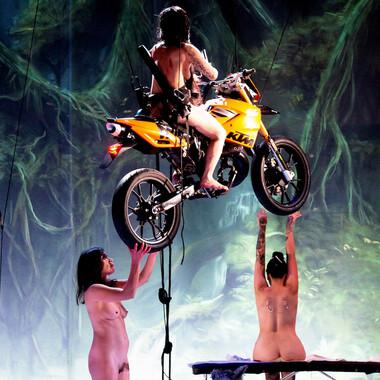 Eine nackte Frau auf einem fliegenden Motorrad. Eine weitere Performerin steht unter dem Motorrad und eine Dritte sitzt im Hintergrund auf einer Bank.