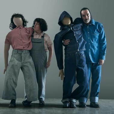 Zwei Personen tragen jeweils eine menschlich anmutende Puppe, indem sie einen Arm der Puppe um ihre Schultern legen und sie an der Taille festhalten. Die Puppen haben kein Gesicht.
