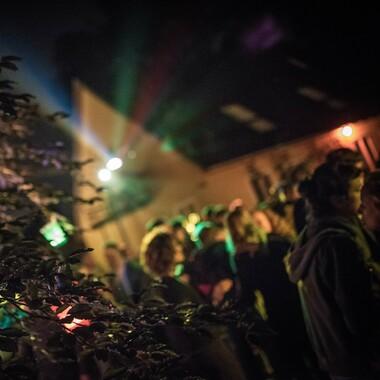 Menschenmenge auf einer Tanzfläche. Das Foto ist unscharf und es sind keine Gesichter zu erkennen. Im Hintergrund ist das zerstreute Licht der Scheinwerfer zu sehen.