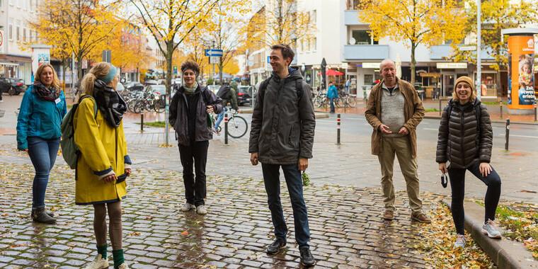Vier Menschen stehen in der Innenstadt.