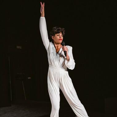 Luanda Casella in einem schicken, weißen Jumpsuit. Eine Hand streckt sie in die Höhe, in der anderen hält sie ein Mikrofon. Ihr linkes Bein macht einen Ausfallschritt.