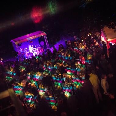 Eine Konzertsituation bei Nacht. Das Foto wurde von oben geschossen und zeigt eine Menschenmenge und eine Bühne, die von unterschiedlich farbigen Scheinwerfern beleuchtet werden.