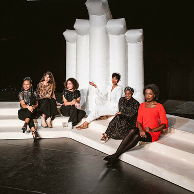 Six performers sit on the steps of the white stage set.