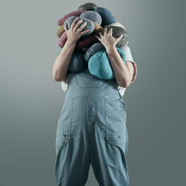 Ein Mensch trägt steinartige Kissen aus den unterschiedlichsten Materialien. Es sind so viele, dass das Gesicht der Person verdeckt ist.