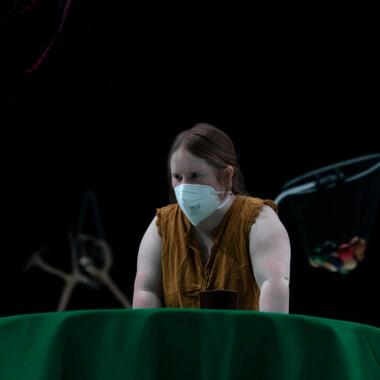 Eine Performerin stützt sich konzentriert mit den Händen auf einem runden Tisch ab. Auf dem Tisch ist eine grüne Tischdecke aus festem Stoff.