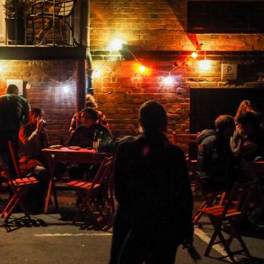Momentaufnahme vom Außenbereich der Feinkost Lampe an einem gut besuchten Abend. Im Hintergrund sind zwei Tische, an denen Menschen sitzen und im Vordergrund ist die Silhouette einer Person zu sehen.