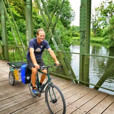 Jemand fährt mit einem Fahrrad über eine Brücke. Am Fahrrad ist ein Anhänger mit Solarpanels.