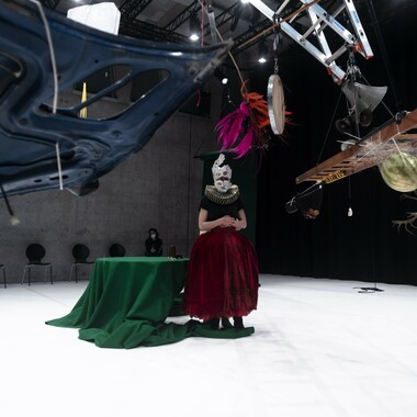 A performer wears a costume with a wide, long skirt and a large fan collar. Her face is masked. Behind her is a round table with a dark green tablecloth. A construct of ladders hangs from the ceiling.