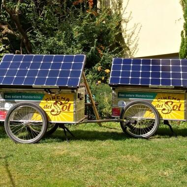 """Zwei Fahrradanhänger mit Solarpanels und dem Schriftzug: """"Cinema del Sol"""""""